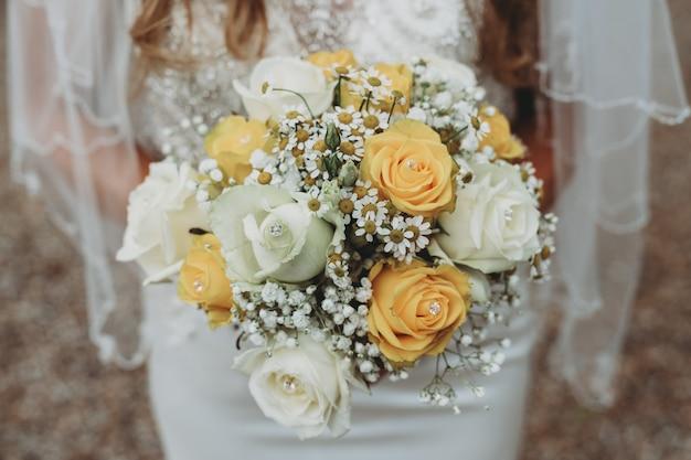 Bruid draagt een trouwjurk met haar traditionele boeket