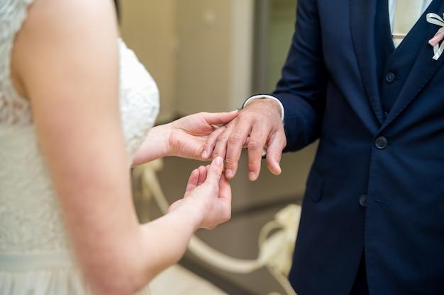 Bruid draagt een trouwring op de bruidegom.