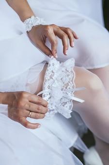 Bruid draagt een witte kanten kousenband op de trouwdag close-up