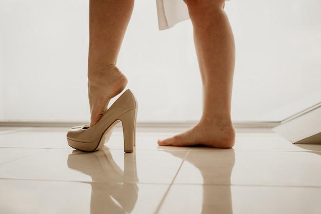 Bruid draagt hoge hak schoen op spiegelvloer in de buurt van panoramisch raam op huwelijksdag