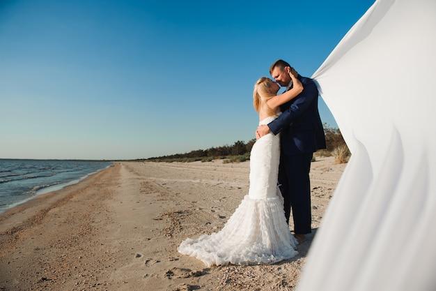 Bruid en bruidegom aan zee op hun trouwdag.