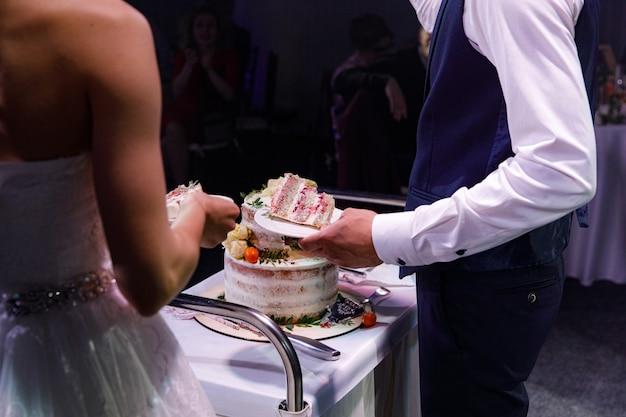 Bruid en bruidegom bij een huwelijksreceptie de bruidstaart aansnijden