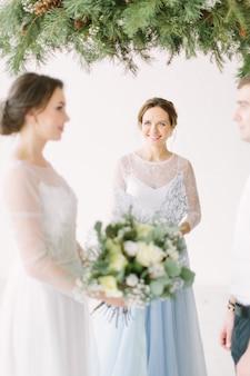 Bruid en bruidegom bij huwelijksceremonie met decoraties en dennenboog in rustieke stijl