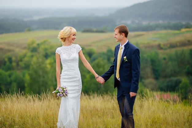 Bruid en bruidegom buiten in de natuur locatie. huwelijkspaar in liefde op huwelijksdag.