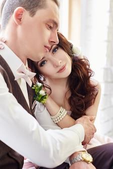 Bruid en bruidegom dichtbij groot venster die vóór huwelijk koesteren