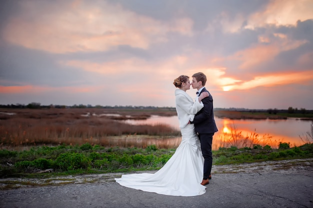 Bruid en bruidegom dichtbij het meer in de avond bij zonsondergang. valentijn dating