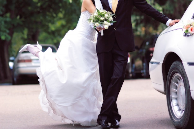 Bruid en bruidegom dichtbij limousine