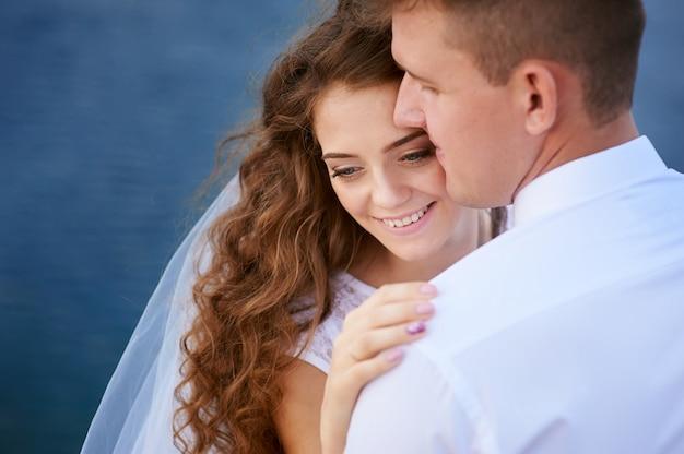 Bruid en bruidegom die bij het meer voor een gang omhelzen.