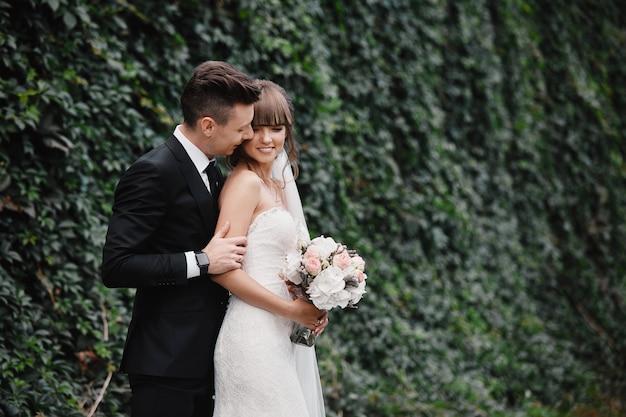 Bruid en bruidegom die bij huwelijksdag in openlucht op de lente groene aard lopen. bruids paar, gelukkige jonggehuwde vrouw en man omarmen in groen park. liefdevolle bruidspaar buiten. bruid en bruidegom