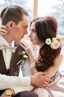 Bruid en bruidegom die dichtbij groot venster vóór huwelijk koesteren