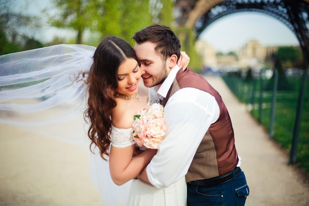 Bruid en bruidegom die een romantisch ogenblik op hun huwelijksdag in parijs hebben