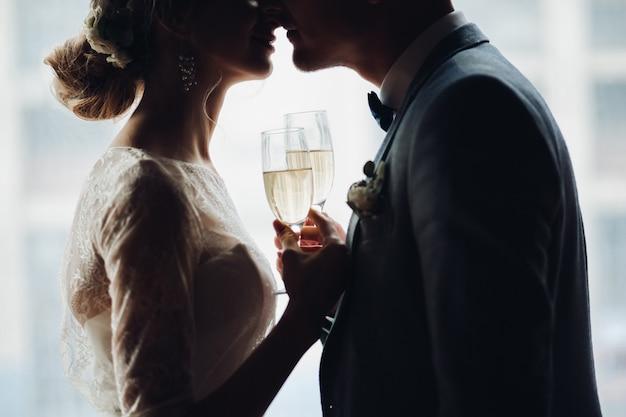 Bruid en bruidegom die en door handen elkaar omhelzen houden