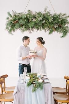 Bruid en bruidegom die huwelijkscake houden die van maaltijd genieten bij huwelijksontvangst die met pijnboom en kaarsen wordt verfraaid