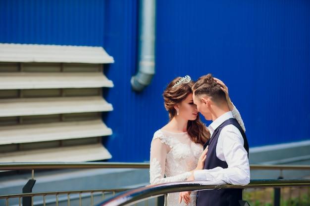 Bruid en bruidegom die in de stad, huwelijksdag, huwelijksconcept lopen. bruid en bruidegom op stedelijke achtergrond. jong koppel gaan op een trap in trouwdag.