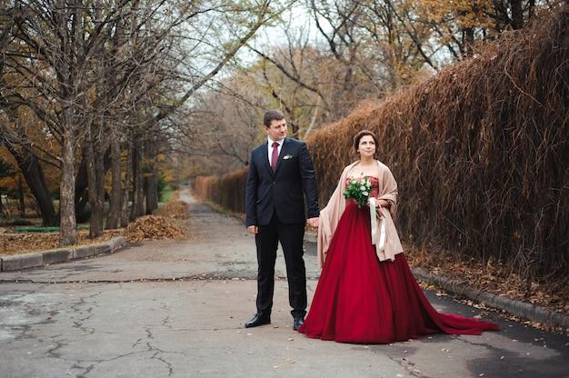 Bruid en bruidegom die in een bos in het de herfstbos koesteren, huwelijksgang