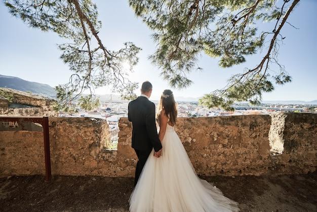 Bruid en bruidegom die in oud kasteel lopen en elkaars hand houden.