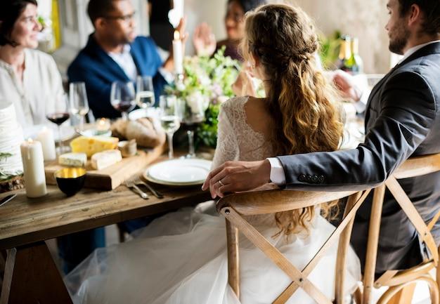 Bruid en bruidegom die maaltijd met vrienden hebben bij huwelijksontvangst