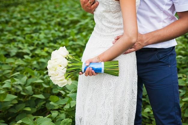 Bruid en bruidegom die mooi huwelijksboeket houden