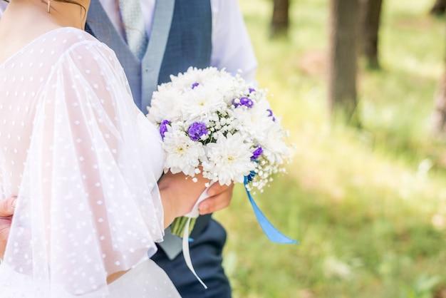 Bruid en bruidegom die mooi huwelijksboeket van bloemen houden.