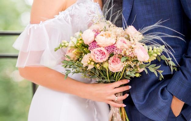 Bruid en bruidegom die mooi huwelijksboeket van bloemen houden