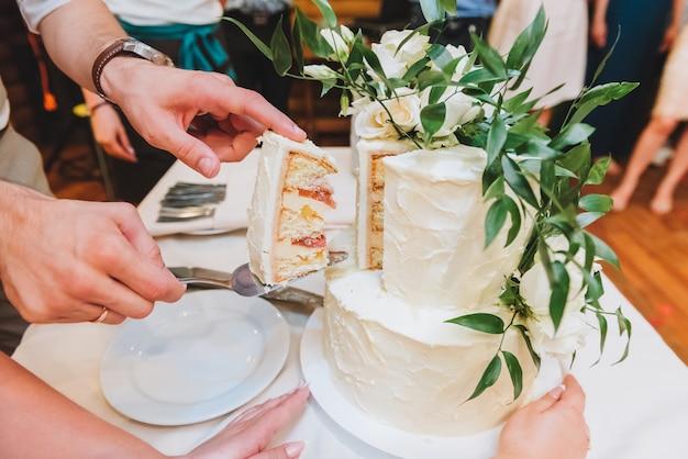 Bruid en bruidegom die mooie huwelijkscake snijden die met bladeren wordt verfraaid