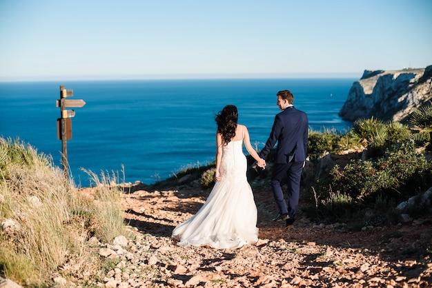 Bruid en bruidegom die op het strand lopen en elkaars hand houden.