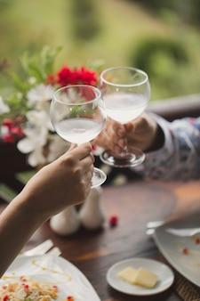 Bruid en bruidegom die prachtig versierde huwelijksglazen houden