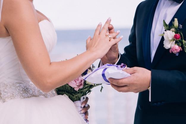 Bruid en bruidegom dragen trouwringen. handen van pasgetrouwden met trouwringen. huwelijksceremonie.