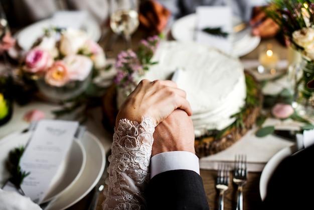 Bruid en bruidegom elkaar de hand op bruiloft receptie