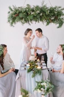 Bruid en bruidegom eten de bruidstaart versierd met dennen, bessen en katoen bloem met hun bruidsmeisjes en groomsmen