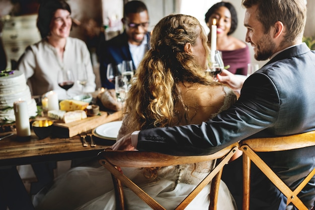 Bruid en bruidegom eten met vrienden bij de receptie van het huwelijk