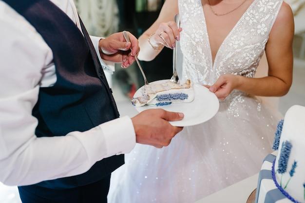 Bruid en bruidegom eten rustieke bruidstaart met delicate violette bloemen.