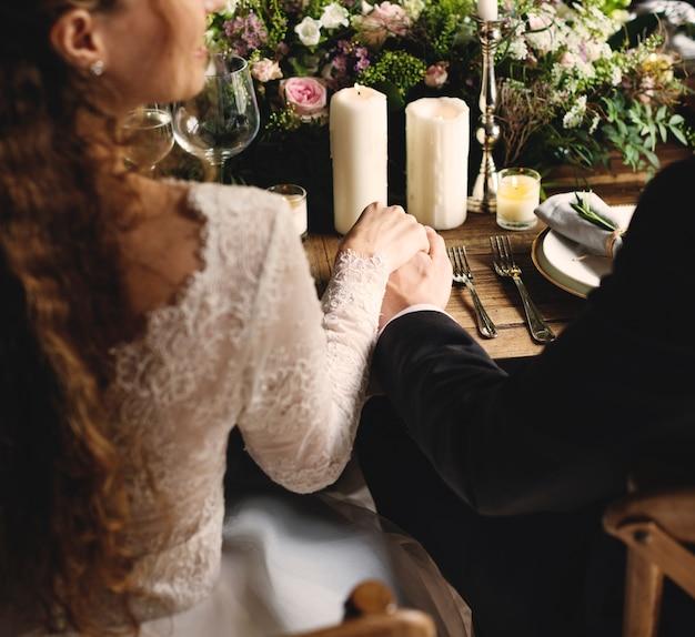 Bruid en bruidegom hand in hand bij de receptie van het huwelijk