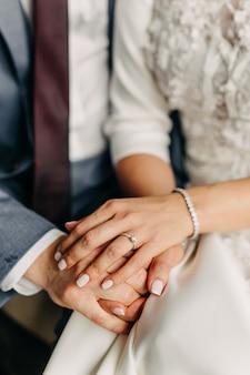 Bruid en bruidegom hand in hand, close-up