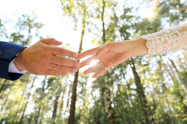 Bruid en bruidegom hand in hand in het park.
