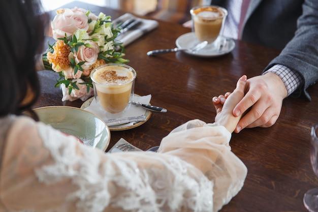 Bruid en bruidegom hand in hand in restaurant.