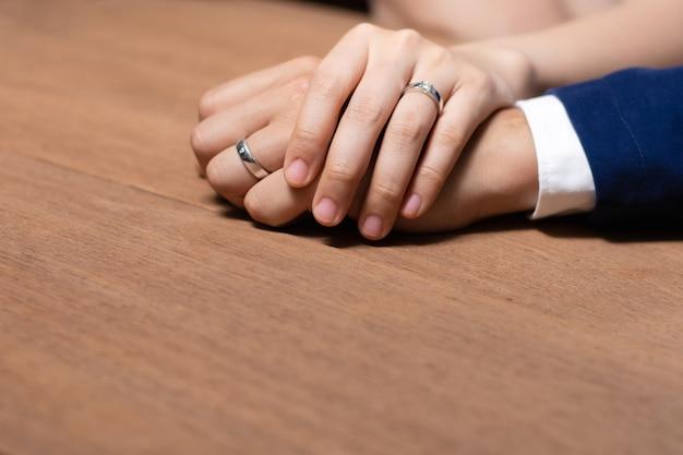 Bruid en bruidegom hand in hand met trouwring op houten tafel.