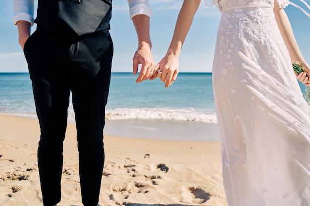 Bruid en bruidegom hand in hand op het strand in trouwjurken
