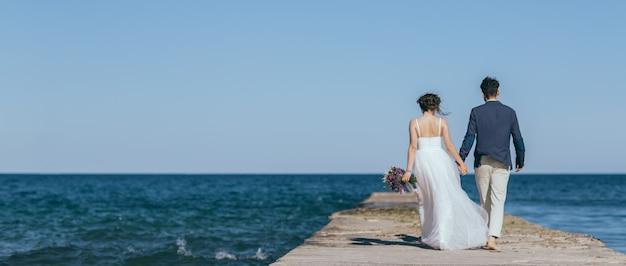 Bruid en bruidegom hand in hand tijdens het wandelen op de pier