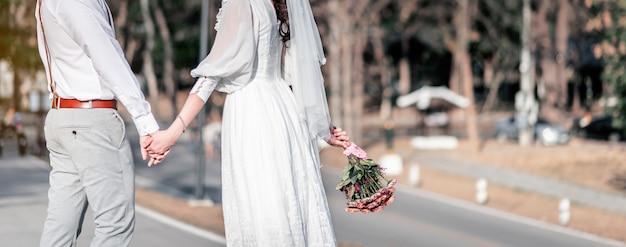 Bruid en bruidegom holding hands buitenshuis in de gebeurtenis van de huwelijksceremonie