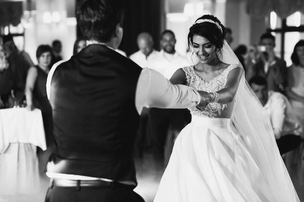 Bruid en bruidegom houden elkaar handen dansen in de hal