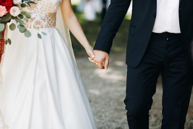 Bruid en bruidegom houden elkaar handen staande voor de boog