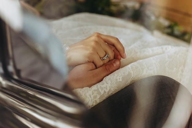 Bruid en bruidegom houden elkaar handen zitten in de auto