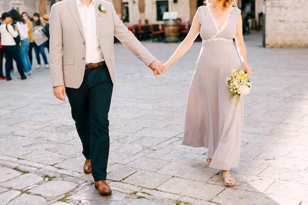 Bruid en bruidegom houden elkaars hand vast op de straatstenen van het stadsplein