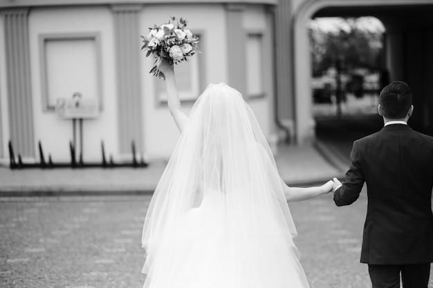 Bruid en bruidegom houden hun handen bij elkaar terwijl ze rondlopen