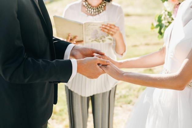 Bruid en bruidegom houden hun handen bij elkaar tijdens de ceremonie