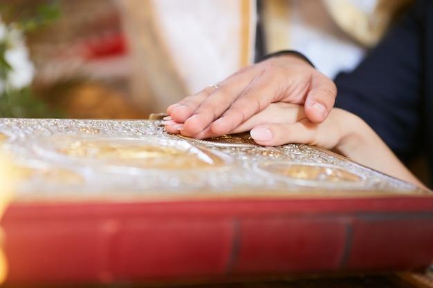 Bruid en bruidegom houden hun handen op de bijbel tijdens de verlovingsceremonie in de kerk