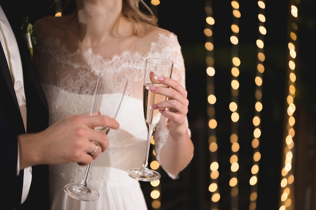 Bruid en bruidegom houden kristallen glazen gevuld met champagne