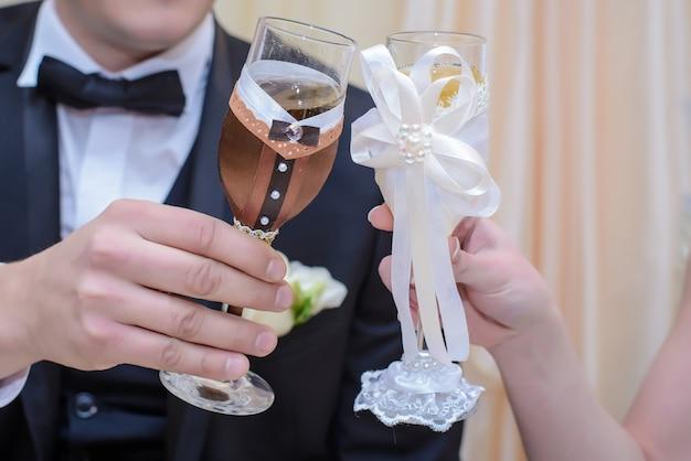Bruid en bruidegom houden mooie bruiloft bril in beige tinten in de handen close-up