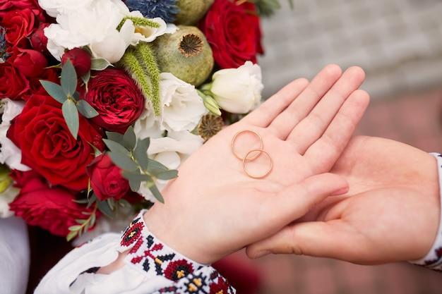 Bruid en bruidegom houden trouwringen in hun armen